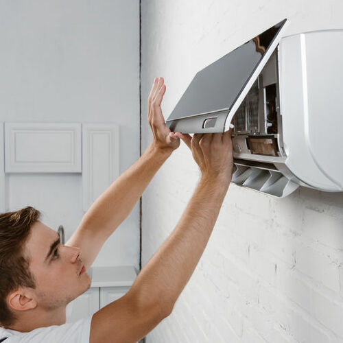 A Man Changes Filter on a Ductless Air Conditioner.