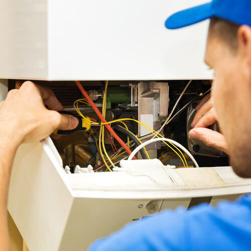A Technician Repairs a Central Heating Unit.