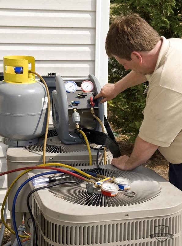 A Man Recharging AC Refrigerant.